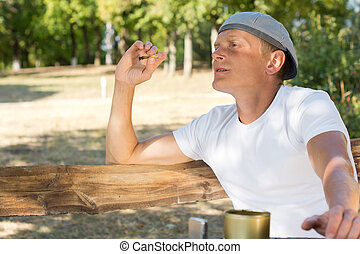 Man sitting smoking in the park - Man sitting smoking a...