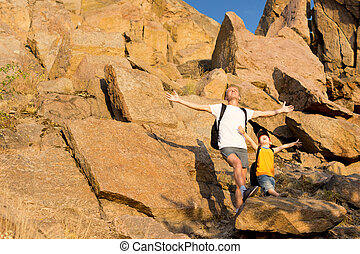 Father and his small son on a rocky mountain standing on a...