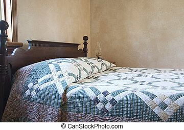 Old fashioned bed with quilt and oil lamp - An old fashioned...