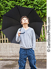 Cool teenage boy - A Teenage boy, outside, holding a black...