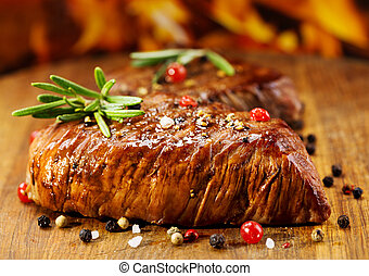 grilled meat with rosemary on wooden table