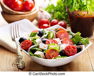 greek salad in a bowl on wooden table