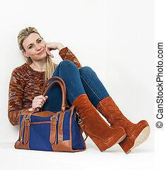 sitting woman wearing fashionable platform brown shoes with a handbag
