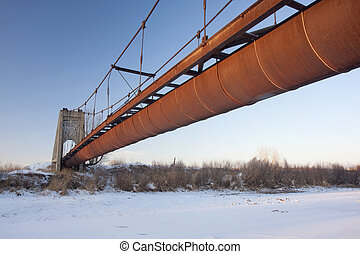 rusty flume suspended over a river