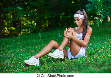 injured sportswoman sitting on the grass