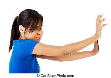 Woman pushing something imaginary isolated over a white...