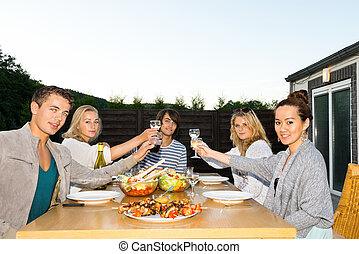 Friends Toasting Drinks At Table During Outdoor Party -...