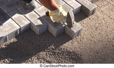 mason worker making sidewalk pavement with stone bricks
