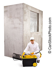 Construction worker with white coveralls, black toolbox and ceme
