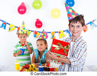Boy with giftbox at birthday party - Handsome boy with...