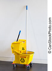 Mop bucket and wringer with caution sign on black floor in...