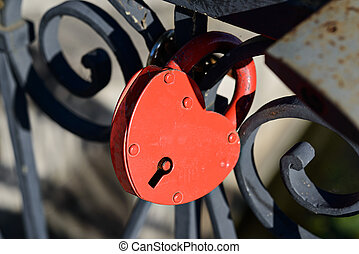Red heart-shaped lock on the bridge