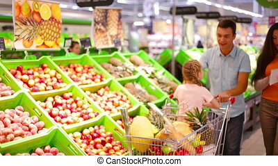 Fruit section - Family of three passing fruit section in the...