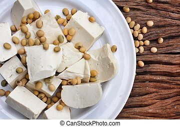 Soybeans and tofu on wood background