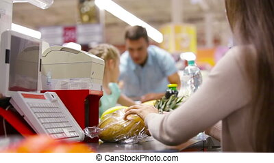 Paying for groceries - Father and daughter paying for...