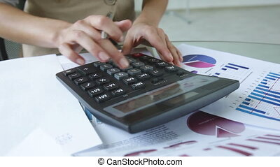 Quick calculations - Close-up of an office worker making...