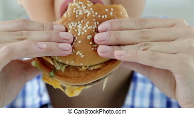 Hamburger eater - Close-up of a girl enjoying a fresh...