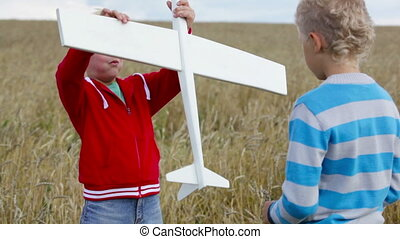 Boys with a toy - Rural boys playing outdoors with a wooden...