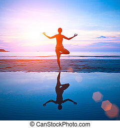 Young woman practicing yoga on the beach at sunset with reflection in water.