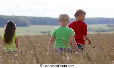 Rural runners - Group of carefree kids running across the...