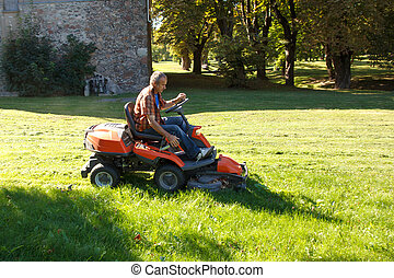 man driving a red lawn mower (tractor)