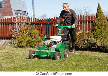 Man working with Lawn Aerator - Lawn Aerator.A lawn aerator...