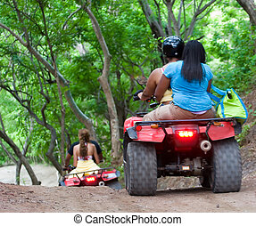 Riding ATVs - People having fun riding ATVs through a...