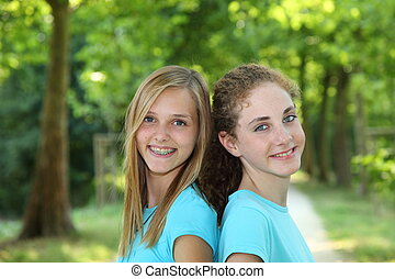 Two happy teenagers standing together in a park - Two happy...