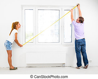 new apartment - couple is measuring their new empty...