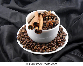 cup of cofee with cinnamon in black background