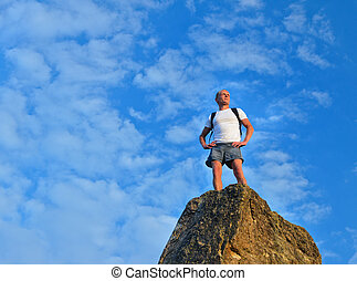 Determined man standing on mountain top after a difficult...