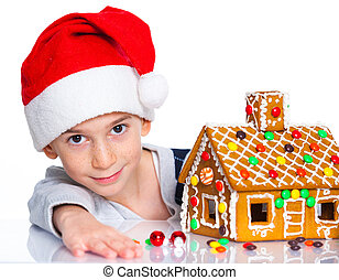 Little boy in Santas hat with gingerbread house - Christmas...