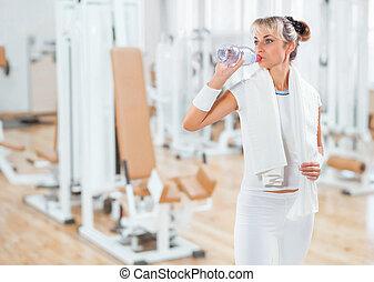 a sportswoman dring water from bottle