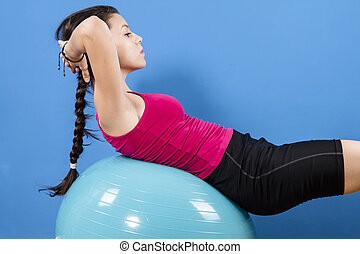 Young women doing pushups on fitness ball.