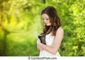 Beautiful woman with Bible is in sunny nature
