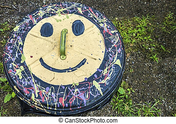 Kind Trash Can - Smiley face painted onto the lid of a trash...