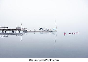 yacht in fog - Yacht and other boats moored at jetty in...