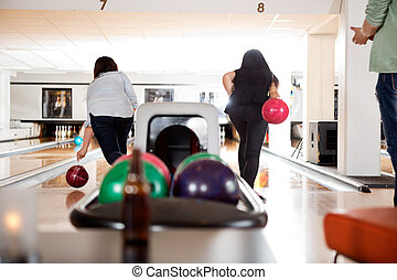 Women Playing in Bowling Alley - Rear view of two women...
