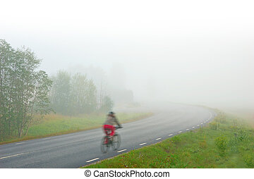 blurred woman in red trousers cycling along rural asphalt road on foggy morning