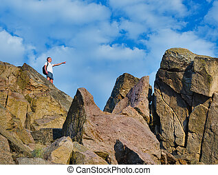 Man on top of a rocky mountain cliff pointing with his arm...