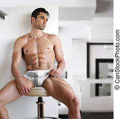 Very sexy young fit manl in white underwear in modern...
