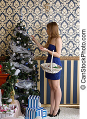 girl dresses up Christmas tree - Young girl dresses up...