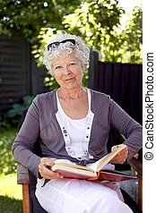 Happy mature woman with novel in garden