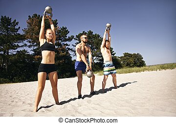 Group of athletes working out with kettle bell on beach -...