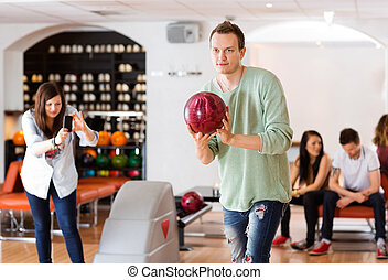 Man Bowling With Friend Photographing in Club - Young man...