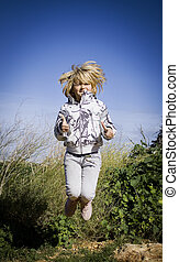 Jumping girl giving thumbs up - A child jumping outside...