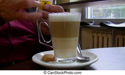 Pouring sugar into coffee latte - Man at a cafe table...