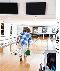 Man Going For The Last Pin in Bowling Alley - Rear view of...