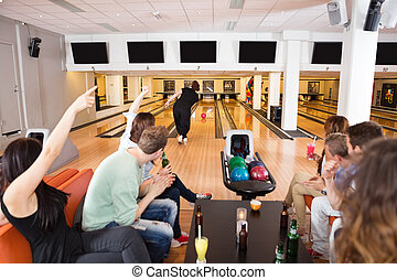 Friends Cheering Woman Bowling in Club - Group of young...