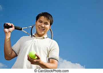 Asian male playing tennis - A happy sporty asian male...